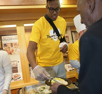 """INDIANAPOLIS - NOVEMBER 20: Myles Turner #33 of the Indiana Pacers serves food to the homeless as the Pacers celebrate, """"Come to House"""" as part of the Pacers Thanksgiving holiday at Bankers Life Fieldhouse on November 20, 2015 in Indianapolis, Indiana. Rodney Stuckey and his wife Heidi, sponsored the event. NOTE TO -- USER: User expressly acknowledges and agrees that, by downloading and or using this Photograph, user is consenting to the terms and condition of the Getty Images License Agreement. Mandatory Copyright Notice: 2015 NBAE (Photo by Ron Hoskins/NBAE via Getty Images)"""